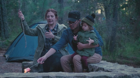 Parents and their daughter roasting marshmallows in a forest