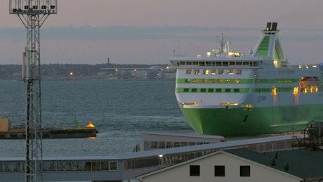Passenger ship entering port at dusk