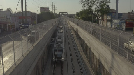 Passenger train traveling between the streets of a city