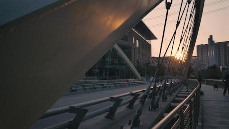 Pedestrian bridge in a city at sunset