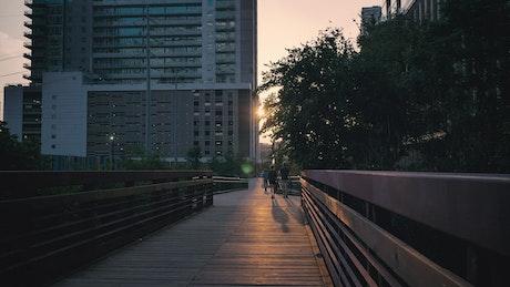 Pedestrian bridge in a city during sunset