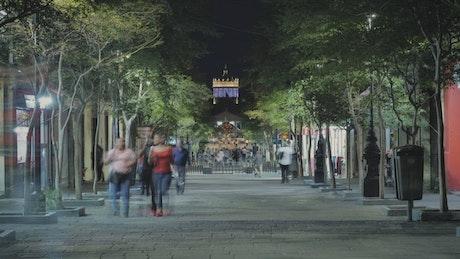 Pedestrian street with people walking at night