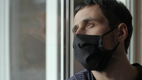 Pensive man in quarantine wearing face mask