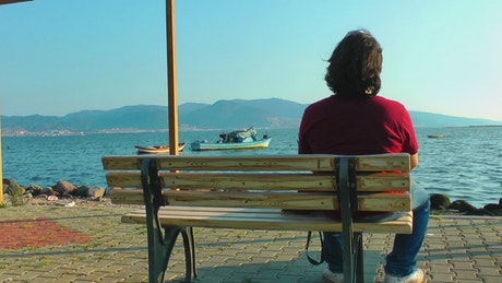 Pensive man looks at the sea from a bench
