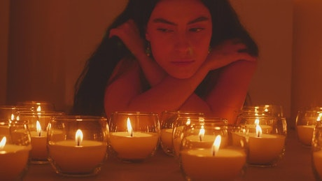 Pensive woman in the dark, surrounded by burning candles