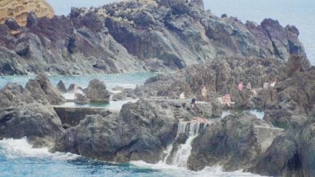 People bathing on the rocks of the seashore