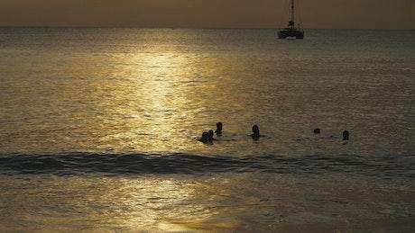 People enjoying the ocean at sunset