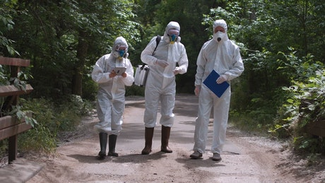People in biohazard suits walking in the forest