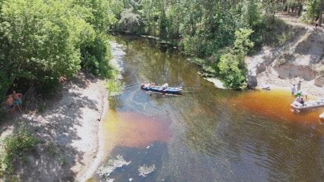 People kayaking along a river, aerial shot