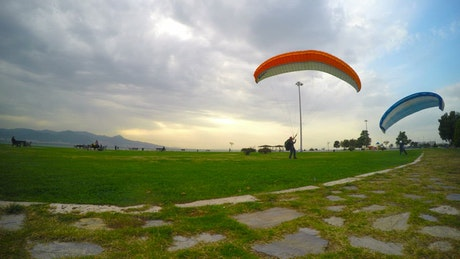 People practicing parachuting on a cloudy day