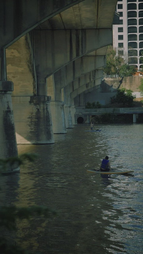 People rowing in a river in the city