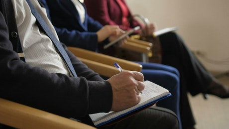 People taking notes during a meeting