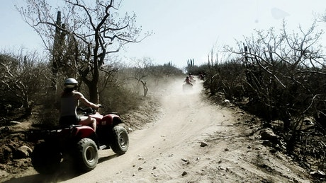 People using all-terrain vehicle on a rugged road