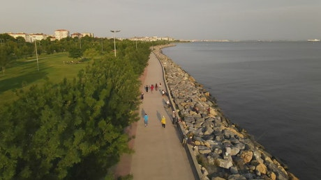 People walking in a park next to the seashore