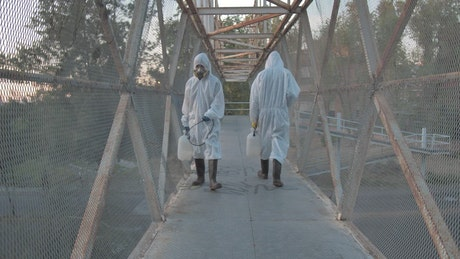 People with masks sanitizing a pedestrian bridge
