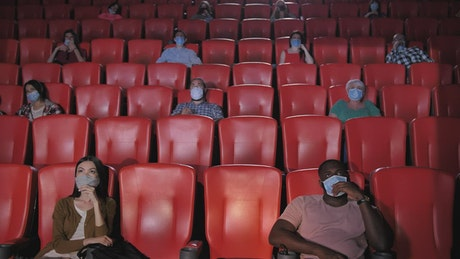 People with masks watching a movie in a cinema