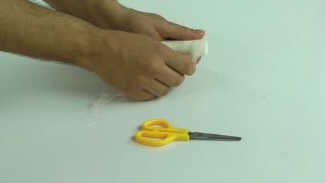Person bandaging himself the hurt hand