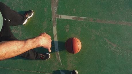 Person bouncing basketball, POV