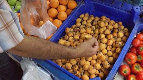 Person choosing fruit in a market