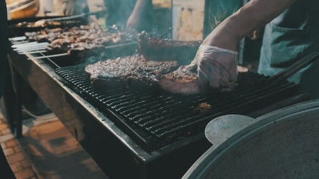 Person cooking cuts of meat on the grill