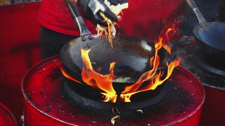 Person cooking in a wok pan with high flame