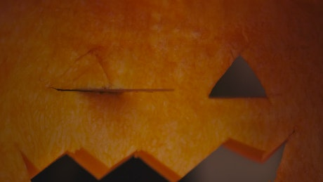 Person cutting a Halloween pumpkin