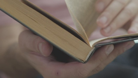 Person flipping through a book looking for a page