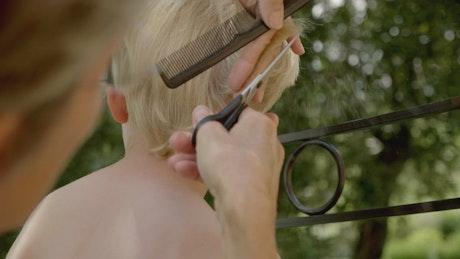Person giving a boy a haircut