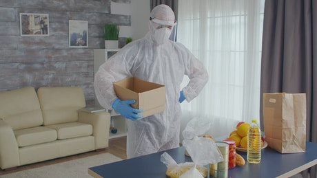 Person in Coronavirus quarantine packs food into box
