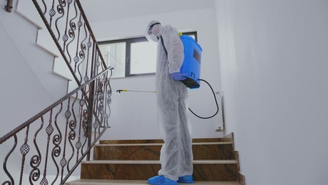 Person in PPE sanitizing building during pandemic