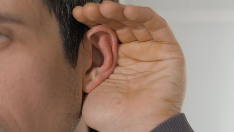 Person places his hand on his ear to hear better