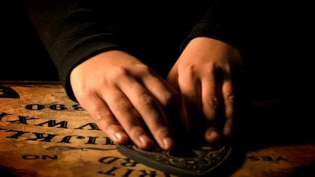 Person playing Ouija board