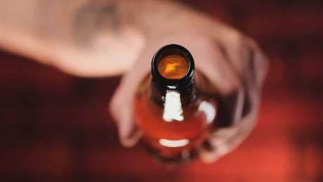 Person pouring beer from a glass bottle