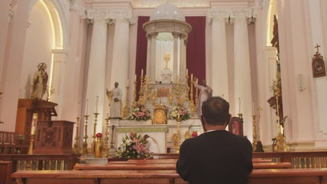 Person praying in front of an altar inside a church