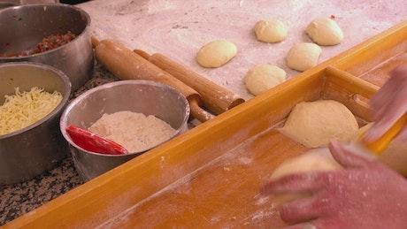 Person preparing pizza dough