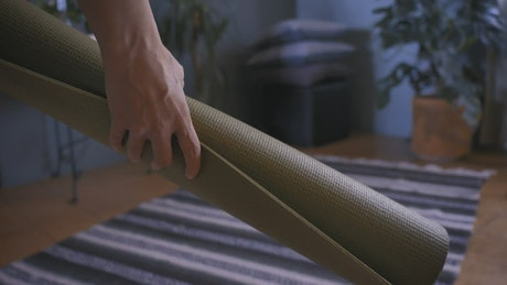 Person putting a yoga mat on the floor