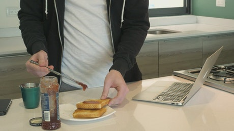 Person putting jam on toast