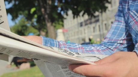 Person reading the newspaper in a park outdoors