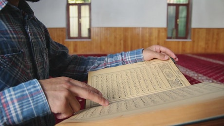 Person reading the Quran inside a mosque