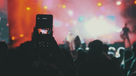 Person recording a concert with his cell phone
