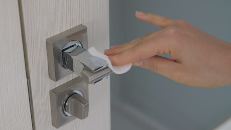 Person sanitizing a doorknob
