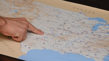 Person searching with his finger a place on a map of USA