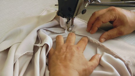 Person sewing a shirt on machine