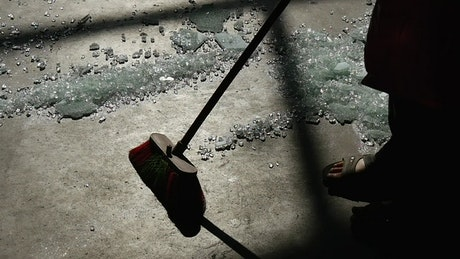 Person sweeping many broken glass from the floor