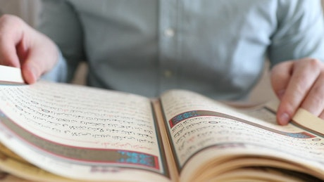 Person turning the sheets of the Quran
