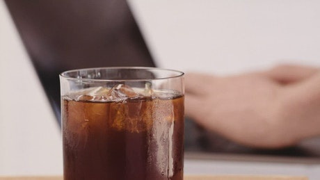 Person typing on a laptop next to a coffee