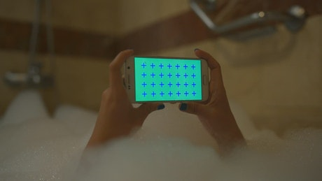 Person with his cell phone in a foam bath