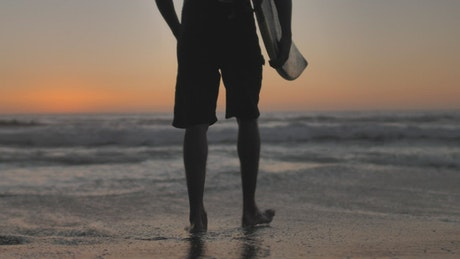 Person with surfboard walks towards waves