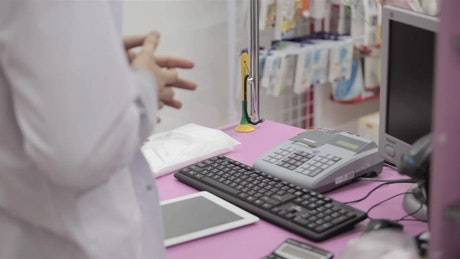 Pharmacy worker accepts payment at checkout