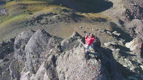 Photografer in the top of a rock in the mountains